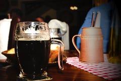 Verre de bière foncée dans un restaurant Images libres de droits