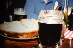 Verre de bière foncée dans un restaurant Image stock