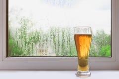 Verre de bière froide sur le rebord de fenêtre un jour pluvieux d'été La vue de la fenêtre Baisses de pluie sur la glace Image stock