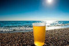 Verre de bière froide sur un fond de la mer Image stock