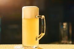 Verre de bière de lumière froide avec la mousse Photo libre de droits