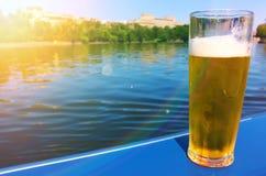 Verre de bière par une rivière Image libre de droits