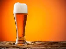 Verre de bière sur le bois avec le fond orange photographie stock libre de droits