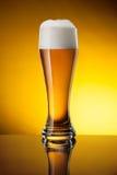 Verre de bière sur le fond jaune Photos libres de droits