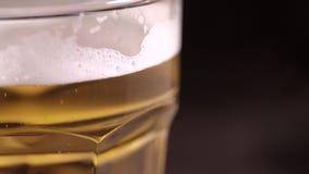 Verre de bière sur un fond noir banque de vidéos