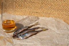 Verre de bi?re blonde et de trois poissons secs sur le papier parchemin? Foyer s?lectif Copiez l'espace images stock