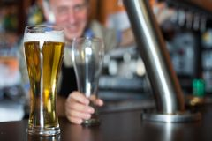 Verre de bi?re sur le compteur de barre sur le fond du barman amical images stock