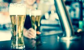 Verre de bi?re sur le compteur de barre sur le fond du barman amical image stock