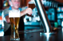Verre de bi?re sur le compteur de barre sur le fond du barman amical photo stock