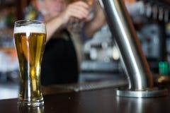 Verre de bi?re sur le compteur de barre sur le fond du barman amical photo libre de droits