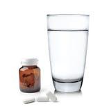 Verre de bouteille et de pilules de médecine de l'eau image stock