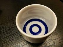 Verre de céramique de saké sur la table en bois Image stock
