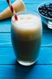 Verre de café de glace avec le cône et de la cuvette de chokeberries sur le colou Photographie stock