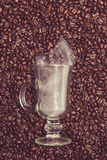 Verre de café irlandais avec de la fumée en grains de café Image stock