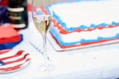 Verre de champagne contre le gâteau à la partie Image stock