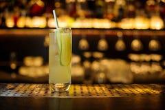 Verre de cocktail alcoolique aigre et amer frais avec le concombre, le jus et le genièvre photo stock