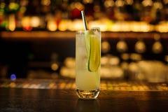 Verre de cocktail alcoolique aigre et amer frais avec le concombre, le jus et le genièvre avec la paille photographie stock