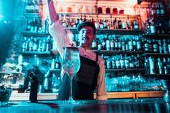 Verre de cocktail ardent sur le compteur de barre dans la perspective des mains de barmans avec le feu photographie stock