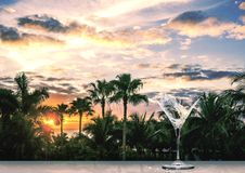 Verre de cocktail avec une éclaboussure de martini sur un coucher du soleil tropical Photographie stock