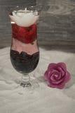 Verre de cocktail dans le sable avec des roses photos stock