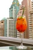 Verre de cocktail orange vibrant de fruit frais de couleur à la barre de dessus de toit, avec les gratte-ciel brouillés à l'arriè photos stock
