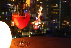 Verre de cocktail rouge vibrant sur la table de la barre de dessus de toit avec le bokeh urbain de vue de nuit à l'arrière-plan photographie stock