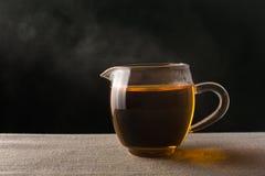 Verre de cuisson à la vapeur chaud de thé noir photos stock