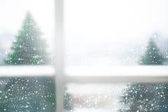 Verre de fenêtre brouillé avec la chute de neige et pins en hiver Photos stock