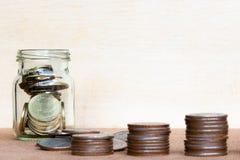 Verre de gamme de pièce de monnaie et de quatre poteaux des pièces de monnaie sur le blurr en bois de vintage Photos stock