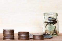 Verre de gamme de pièce de monnaie et de quatre poteaux des pièces de monnaie sur le blurr en bois de vintage Photos libres de droits