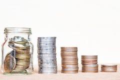 Verre de gamme de poteau de pièce de monnaie et de quatre piles des pièces de monnaie sur la tache floue de vintage images libres de droits