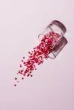 Verre de jour de valentines avec un bon nombre de coeurs doux de sucrerie Photo stock