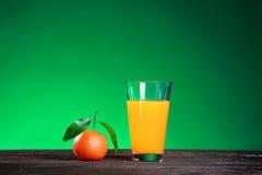 Verre de juise et mandarine douce mûre avec la feuille sur le vert Photos libres de droits