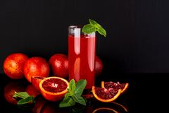 Verre de jus avec des quelques morceaux d'orange sicilienne sur un fond noir Orangeade sicilienne photos stock