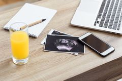 verre de jus, de balayage d'ultrason de bébé à venir et de dispositifs numériques photographie stock