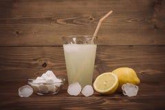 Verre de jus de citron frais avec la moitié découpée en tranches de citron Images stock