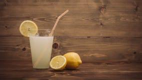 Verre de jus de citron frais avec la moitié découpée en tranches de citron Images libres de droits