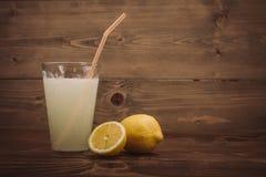 Verre de jus de citron frais avec la moitié découpée en tranches de citron Photo libre de droits