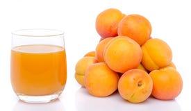 Verre de jus d'abricot à côté d'un tas des abricots Images libres de droits