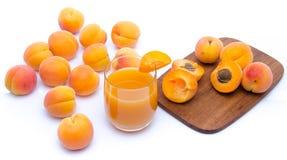 Verre de jus d'abricot avec les abricots entiers et coupés en tranches Photos stock