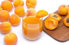Verre de jus d'abricot avec les abricots entiers et coupés en tranches Image stock