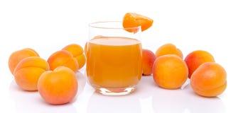 Verre de jus d'abricot entouré avec des abricots Photographie stock
