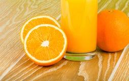 Verre de jus d'orange avec l'orange et les moitiés Image libre de droits