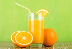Verre de jus d'orange avec la tranche sur le fond vert Photo libre de droits