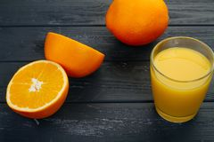 Verre de jus d'orange et d'orange sur le fond gris Image stock