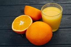 Verre de jus d'orange et d'orange sur le fond gris Photo stock