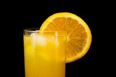 Verre de jus d'orange frais avec de la glace et une tranche d'orange d'isolement sur le fond noir Image stock