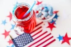 Verre de jus et drapeau américain le Jour de la Déclaration d'Indépendance Images stock