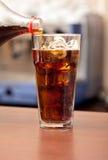 Verre de kola avec de la glace sur la barre Photographie stock