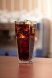 Verre de kola avec de la glace sur la barre Photo libre de droits